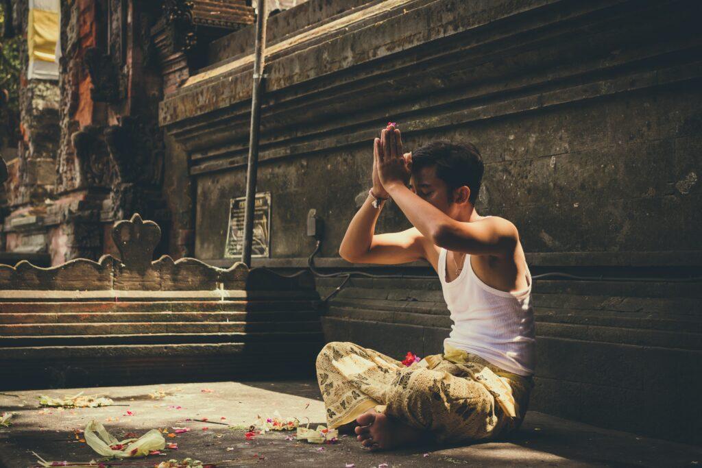 en religiøs mand sidder på jorden med krydsede ben og armene over hovedet, mens han beder en bøn