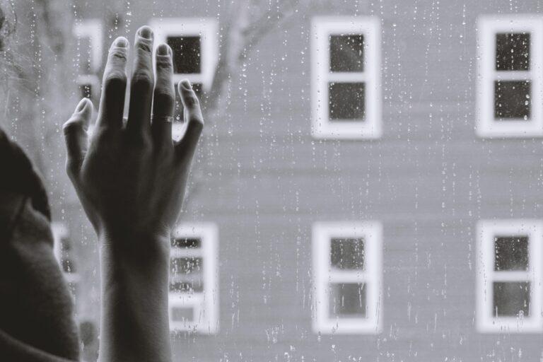 en hånd på et vindue dækket af regndråber