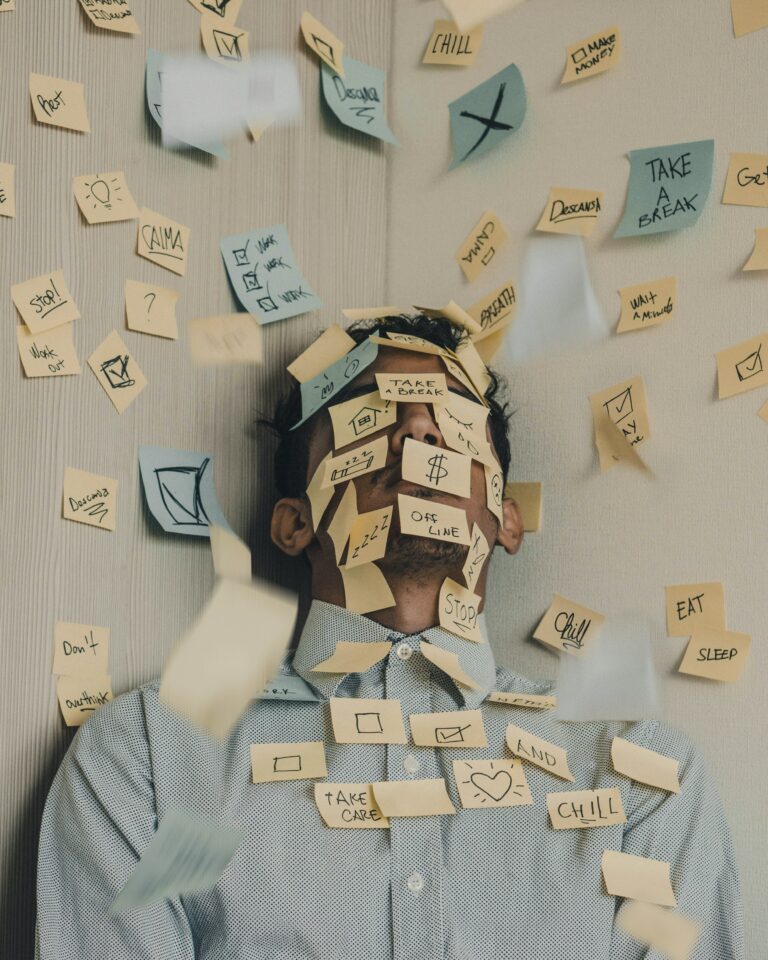 træt mand sidder med post-it noter klistret over hans ansigt, på noterne er der skrevet stressende faktorer