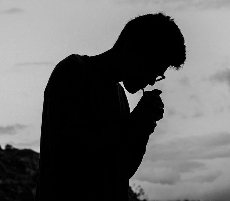 silhuet af en mand der tænder en cigaret