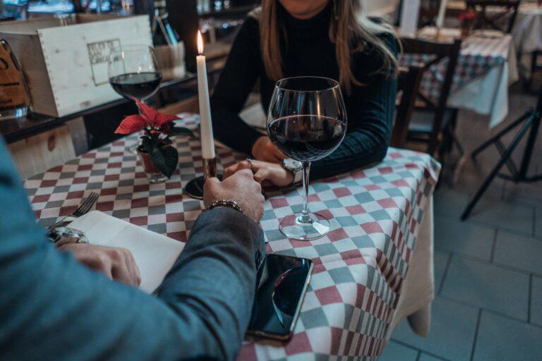 en mand og kvinde sidder på en restaurant og holder hinanden i hånden